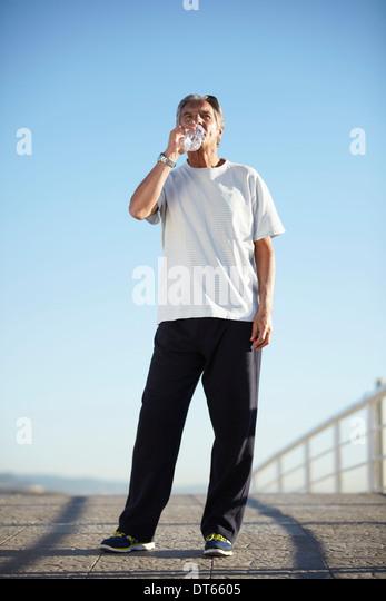 Senior man drinking water on walk - Stock Image