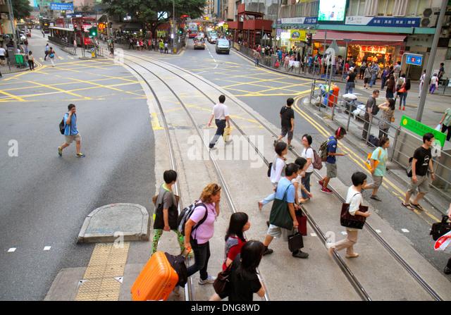 China Hong Kong Island Wan Chai Hennessy Road pedestrians crossing street tracks - Stock Image
