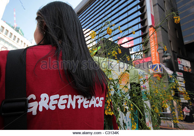 A Greenpeace activist marches with a crowd of 5,000 in Shibuya, calling on the Japanese government to abandon nuclear - Stock Image