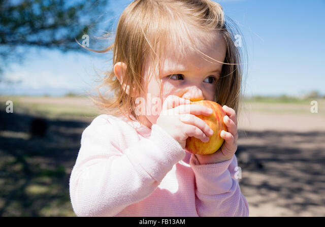 Portrait of girl (2-3) eating apple - Stock Image