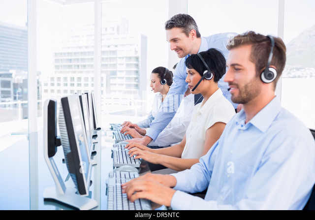 Manager and executives with headsets using computers - Stock Image