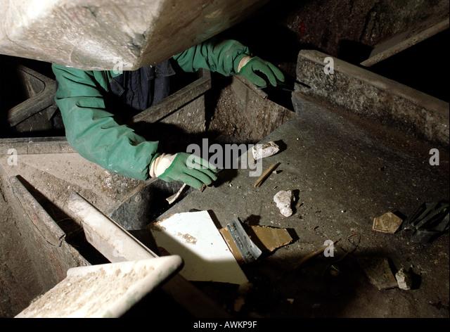 Worker separating trash falling down chute - Stock Image