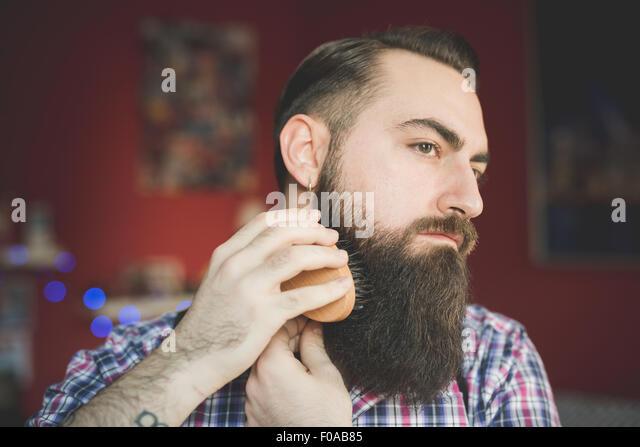 Young bearded man brushing his beard - Stock-Bilder