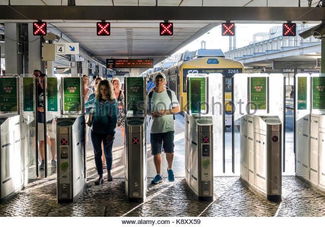 Portugal Lisbon Cais do Sodre railway station suburban train terminus platform turnstile exit man woman Hispanic - Stock Image