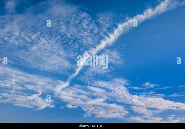 Contrail (or chemtrail) in cloudy sky - France. - Stock Image