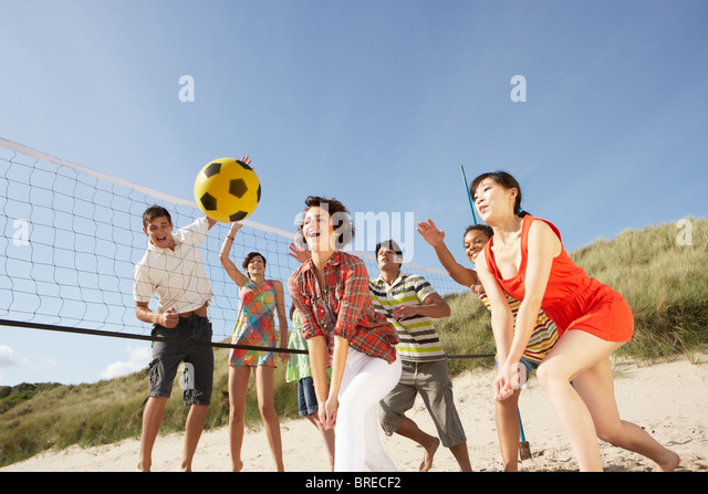 Group Of Teenage Friends Playing Volleyball On Beach - Stock Image