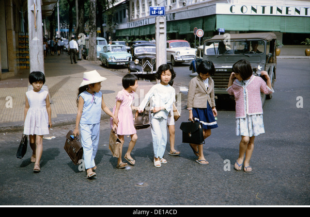 Vietnam War 1957 - 1975 Vietnamese schoolchildren on the street near Hotel Continental Saigon South Vietnam 1965 - Stock-Bilder