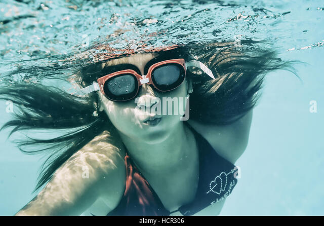 Little girl swimming underwater in sea - Stock Image