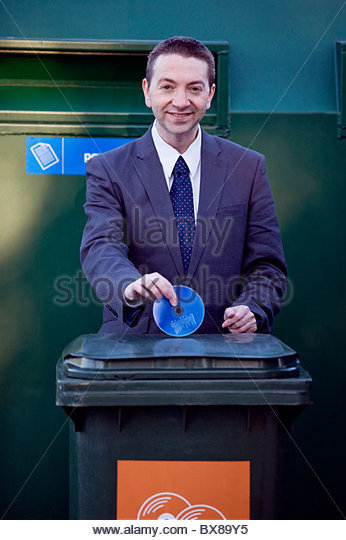 A businessman recycling a cd - Stock Image