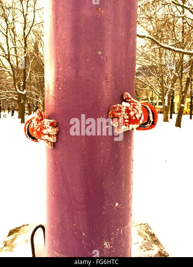 Cropped Hands Wearing Gloves While Hugging Architectural Column On Snowy Field - Stock-Bilder