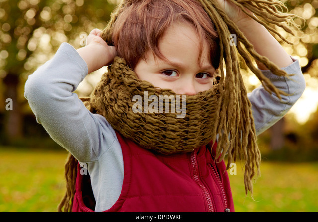 Boy in park, with scarf covering mouth - Stock Image
