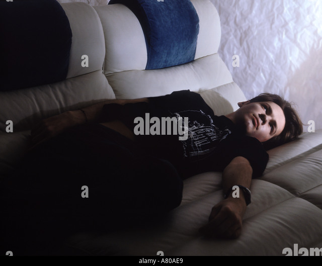 Young man lying on the sofa - Stock Image