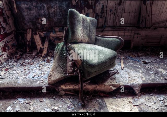 Broken chair in decayed room - Stock Image