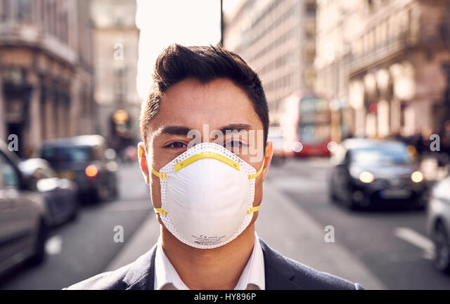 A young Japanese man wears a filter mask in London - Stock Image