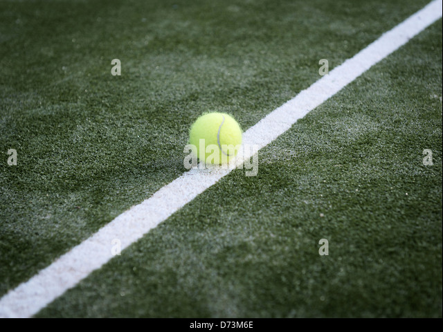 Tennis ball on a line. - Stock Image