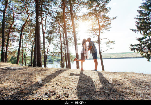 Romantic couple on the beach at colorful sunset  background - Stock Image
