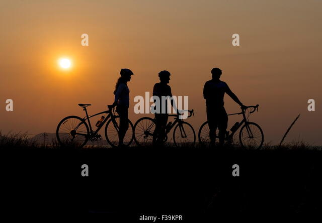 Silhouette of three cyclists at sunset - Stock Image