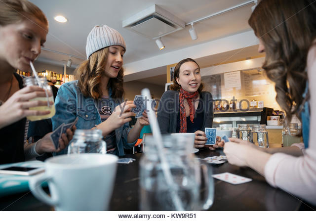 Tween girl friends playing cards at cafe table - Stock Image
