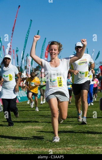 Runner celebrates at the finish of the 5km Fun Run, Two Oceans Marathon, Cape Town, South Africa - Stock Image