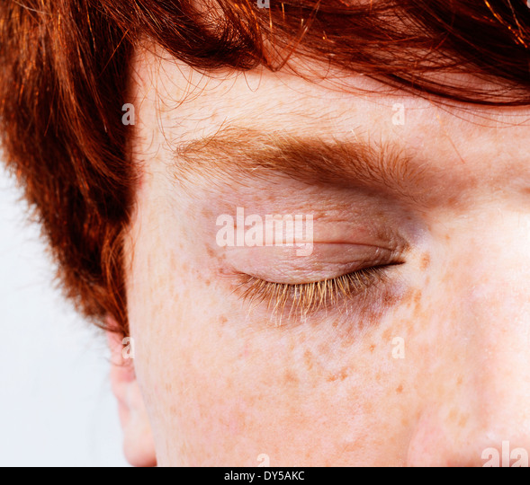 Partial facial shot of young man with red hair and freckles, eyes closed - Stock-Bilder
