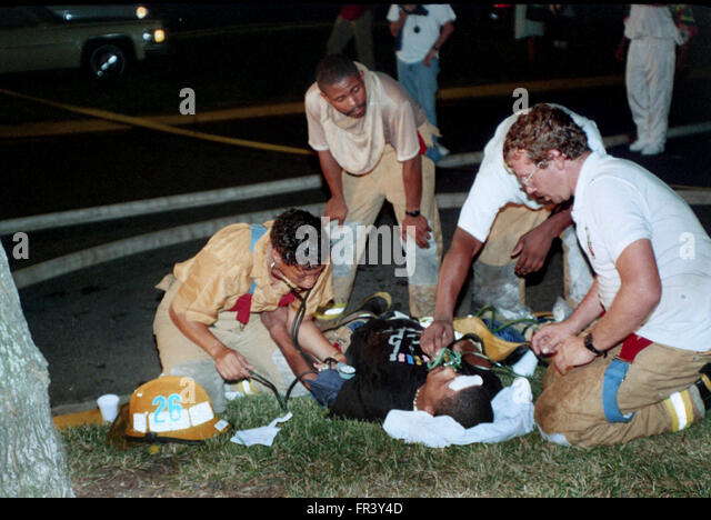 Medics working on firefighter who collapsed after being overcome with heat and smoke at a house fire in Seat Pleasant, - Stock Image