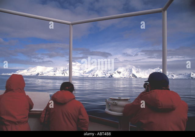 ANTARCTICA Cruise People look at distant sunlit shore mountains  South Shetlands - Stock Image
