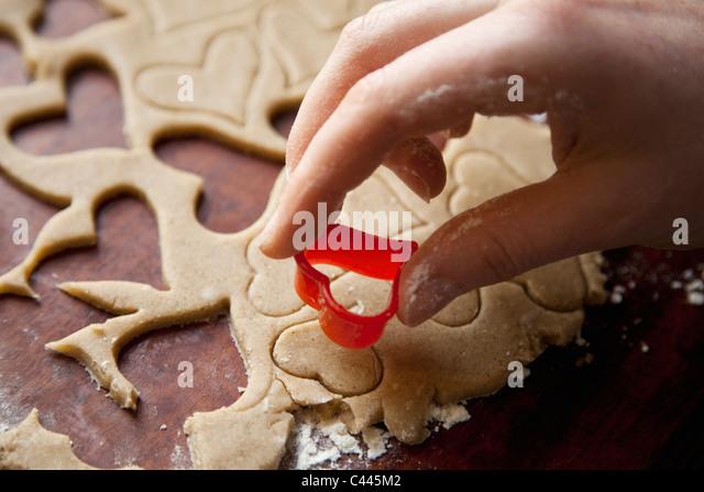 Detail of a hand using a heart shape cookie cutter - Stock-Bilder