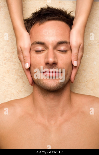 Germany, man receiving facial massage, close-up - Stock Image