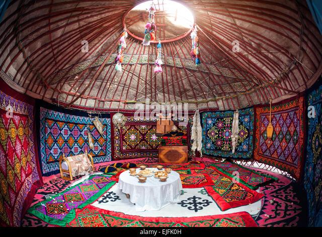 Ethnic nomadic house yurt interior with table of national food at Nauryz celebration - Stock Image
