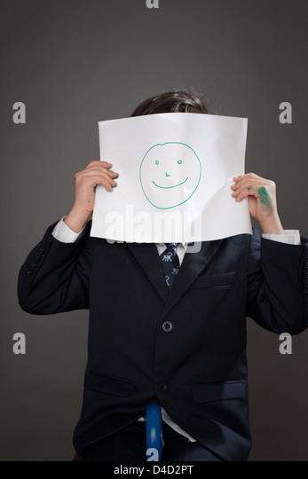 Boy covering face with drawing of happy face - Stock-Bilder