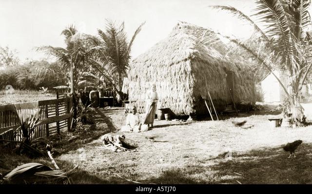 Historical photo of Hawaiian family and grass shack - Stock Image