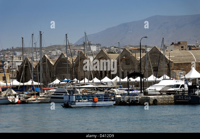 The port of Chania, Crete, showing the vaulted shipyard buildings of the Venetian Arsenali - Stock Image