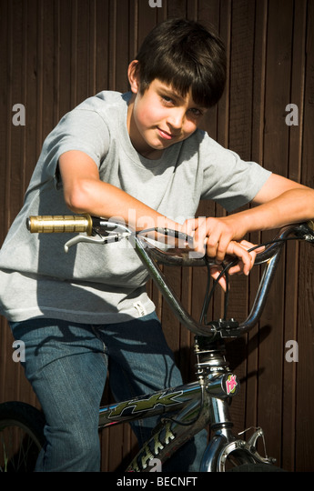 boy boys bike bmx on ride cycle cyclist cycling kid riding kids cool trendy fashionable smile smiling young man - Stock Image