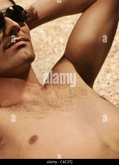 Bare-chested man sunbathing on beach - Stock Image