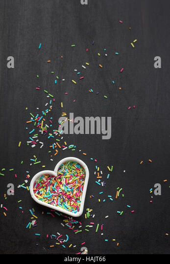 Heart shaped cookie cutter with candy sprinkles - Stock Image