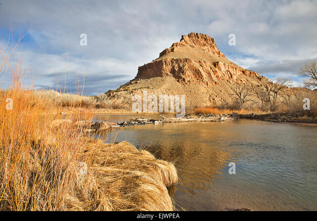 The Chama River flows beneath rugged cliffs of colored earth near the village of Abuiquiu in northern New Mexico, - Stock Image