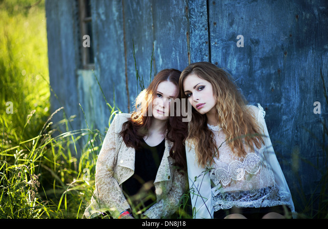 Two women leaning against a house wall - Stock Image