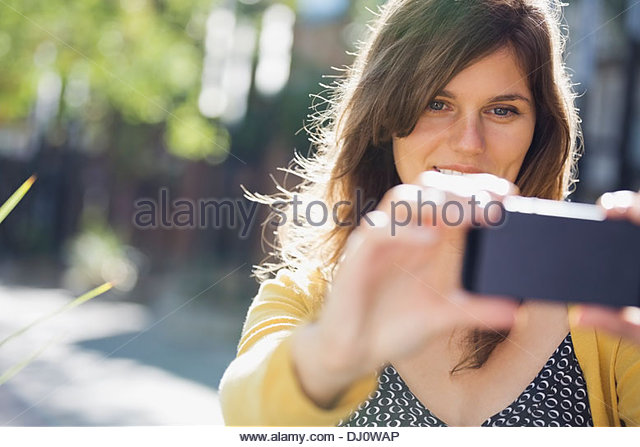 Woman photographing outdoors - Stock Image