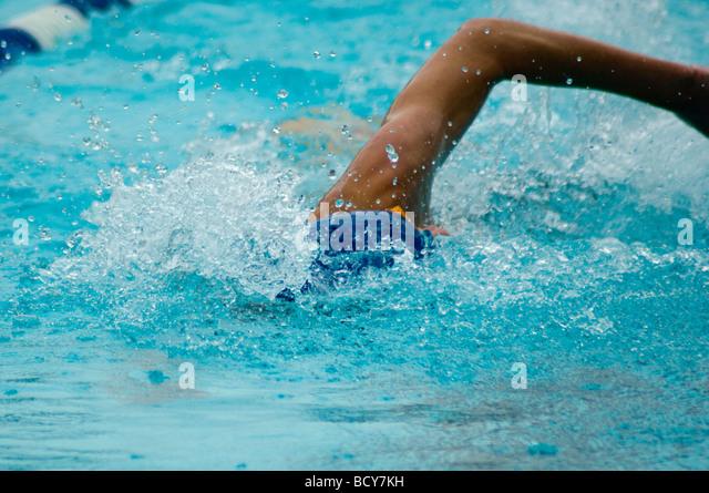 Teen male in swim cap in mid-stroke - Stock Image