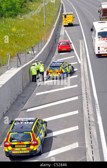 Red car involved in motorway crash moved to hard shoulder whilst traffic police investigate - Stock Image