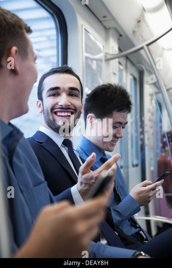 Three businessmen sitting in a row and talking on the subway - Stock Image
