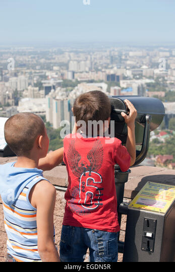 Boys looking at view of Almaty from Kok Tobe mountain, Almaty, Kazakhstan - Stock Image