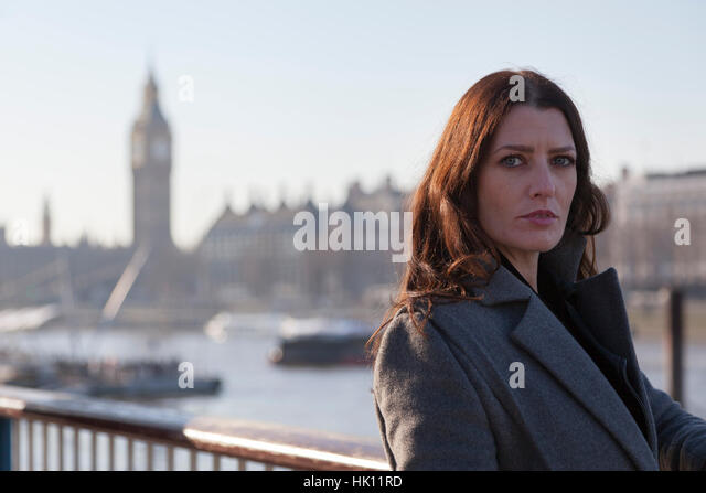 An attractive woman with long dark hair standing by the River Thames with Big Ben and other London  landmarks in - Stock Image