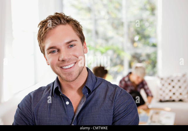 Close-up of smiling man looking at camera with friends in the backgrounds - Stock-Bilder