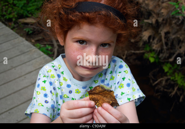A young girl warily displays a found caterpillar. - Stock Image