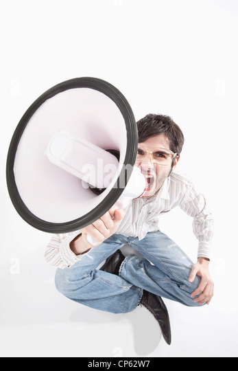 Young man with crazy glasses and megaphone, portrait - Stock Image