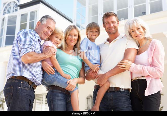 Extended Family Outside Modern House - Stock Image