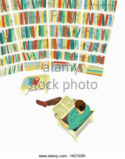 Man relaxing reading in library surrounded by shelves of books - Stock-Bilder