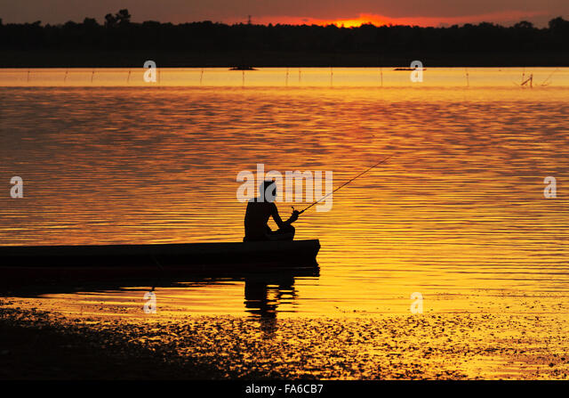 Silhouette man sitting in a boat fishing at sunset - Stock Image