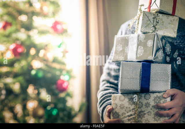 Person holding stack of christmas gifts - Stock Image